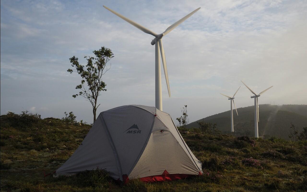 Zelt vor Windrad in Nordspanien
